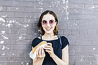 Portrait of smiling woman with Hot Dog in front of wall - GIOF01866