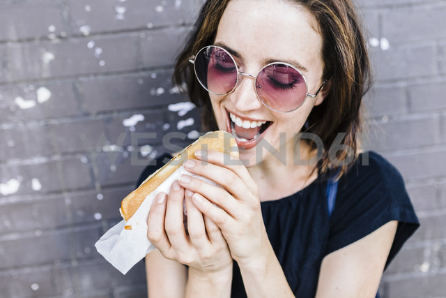 Portrait of woman eating a Hot Dog - GIOF01869