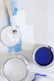 Used paint brush and paint tins with blue and white varnish - CMF00640