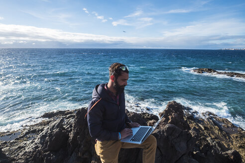 Spain, Tenerife, man using laptop in front of the sea - SIPF01412