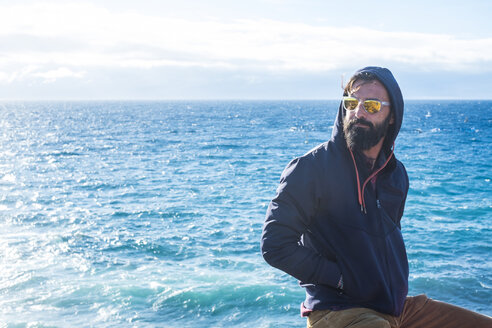 Portrait of man wearing mirrored sunglasses and hooded jacket in front of the sea - SIPF01418