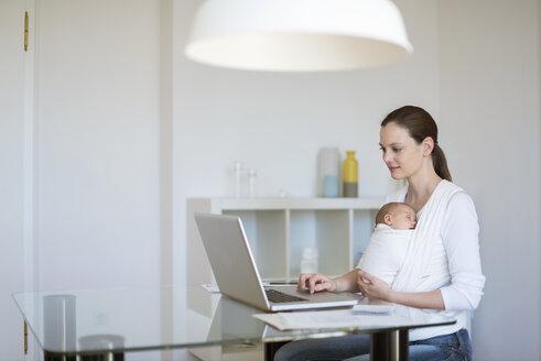 Mother with baby girl in sling working from home - DIGF01506