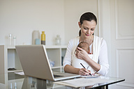 Mother with baby girl in sling working from home - DIGF01509