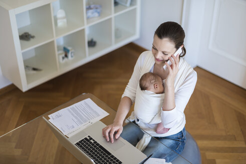 Mother with baby girl in sling working from home - DIGF01515
