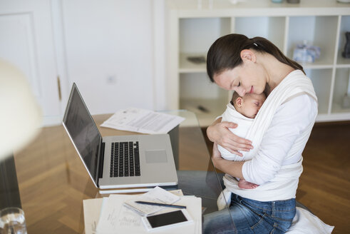 Mother with baby girl in sling working from home - DIGF01521