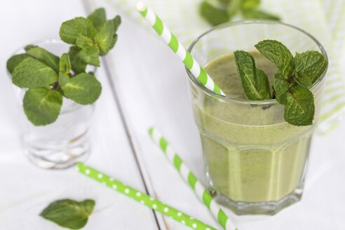 Glass of green smoothie garnished with mint leaves - YFF00647