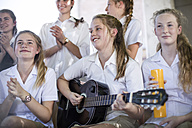 Female high school student playing guitar with group of school friends outside - ZEF12814