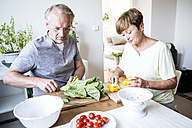 Senior couple in kitchen preparing salad together - WESTF22669