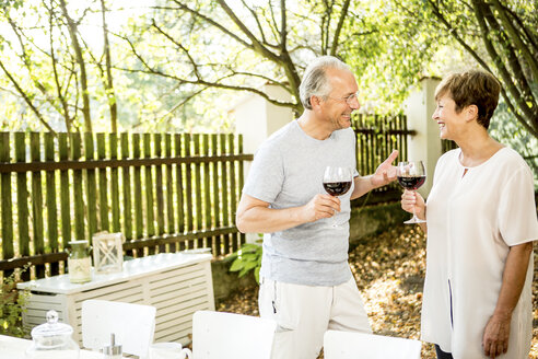 Happy senior couple having glass of red wine outdoors - WESTF22693