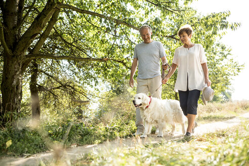 Senior couple going walkies with dog - WESTF22705