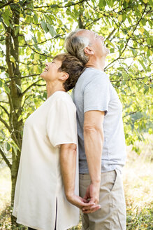 Happy senior couple stading back to back outdoors - WESTF22711
