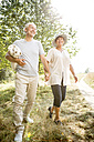 Happy senior couple walking with blanket in nature - WESTF22726