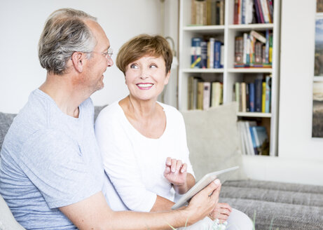 Senior couple at home sitting on couch using digital tablet - WESTF22729
