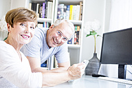 Senior couple at desk with digital tablet - WESTF22732