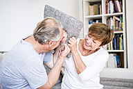 Carefree senior couple at home having a pillow fight - WESTF22744