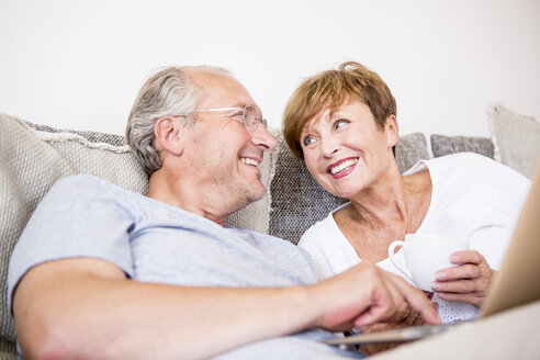Happy senior couple at home sitting on couch using laptop - WESTF22747