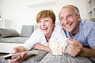 Happy senior couple at home lying on couch watching Tv - WESTF22753