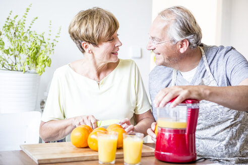Senior couple in kitchen preparing freshly squeezed orange juice - WESTF22759