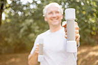 Senior man exercising with dumbbells outdoors - WESTF22765
