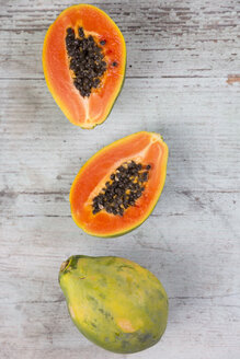 Whole and sliced papaya on wood - JUNF00838