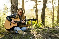 Young woman playing guitar in nature - KKAF00415
