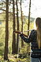 Young woman playing guitar in nature - KKAF00418