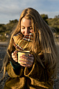 Smiling young woman holding hot drink in nature - KKAF00424