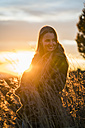 Smiling young woman in nature at sunset turning around - KKAF00442