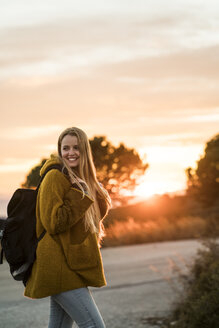 Smiling young woman in nature at sunset turning around - KKAF00445