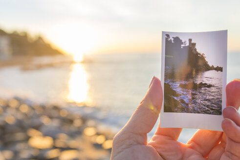Spain, Costa Brava, Lloret de Mar, woman's hand holding instant photo of Castillo de los Plaja near by - SKCF00257