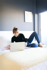 Young woman lying on bed using laptop - VABF01109