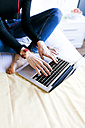 Woman on bed using laptop - VABF01112