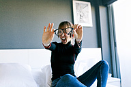 Young woman on bed holding her glasses - VABF01121