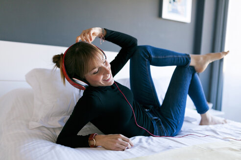 Happy young woman lying on bed wearing headphones - VABF01124