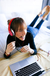 Young woman lying on bed with laptop wearing headphones - VABF01127