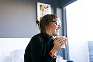 Happy young woman at home drinking cup of coffee - VABF01130