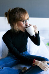 Young woman sitting on bed drinking cup of coffee - VABF01133