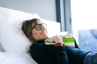 Smiling young woman lying on bed with book - VABF01136
