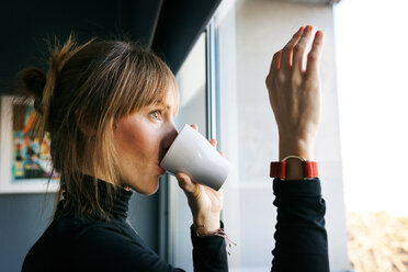 Young woman drinking cup of coffee looking out of window - VABF01139