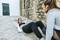 Two young womwn doing strength training in the steet - KIJF01223