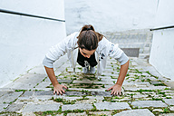 Young woman doing push ups in the street - KIJF01226