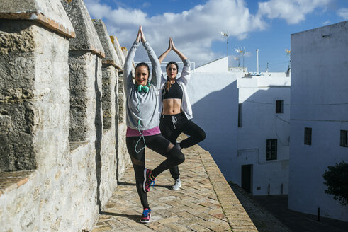 Two young women exercising yoga in the street - KIJF01238