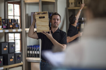 Man carrying crate of wine in shop - ZEF12855