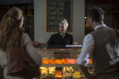 Saleswoman behind counter at food store - ZEF12861