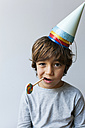 Portrait of little boy with lollipop and four party hats on his head - VABF01151