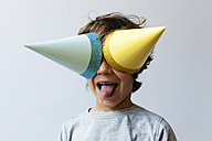 Portrait of little boy with two party hats on his eyes sticking out tongue - VABF01154