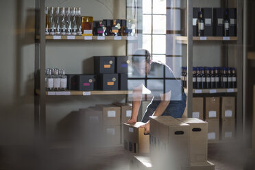 Man packing bottles of wine in shop - ZEF12863