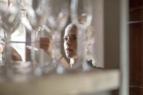 Waitress examining wine glasses - ZEF12869