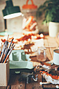Table with pot of paintbrushes, plastic animals, lamp and plant in the background - RTBF00675