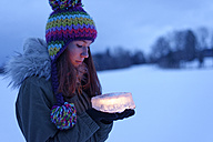 Teenage girl holding cake made of ice with candle inside - LBF01566
